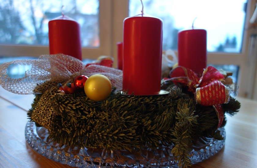 Foto: Adventskranz mit 4 roten Kerzen vor einem Fenster