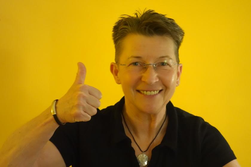 Foto von Aufräumcoach Rita Schilke vor gelber Wand