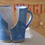"""Zerbrochene Tasse mit Schriftzug """"Fragile"""" im Hintergrund"""